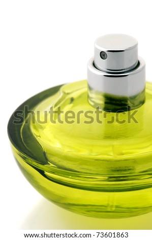 Opened bottle of green perfume close-up on white background. - stock photo