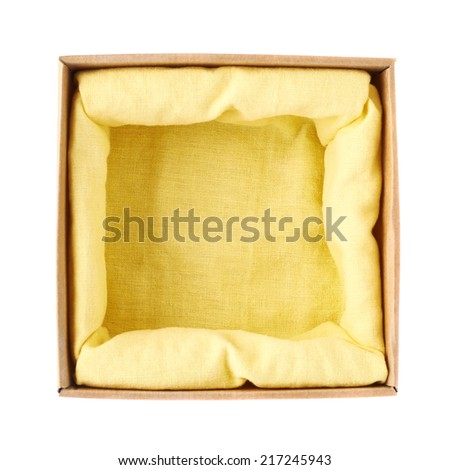 Opened cardboard box with the yellow cloth inside, isolated over the white background, top view - stock photo