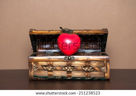 Opened decorative chest with heart on wooden table. Valentine day concept. - stock photo