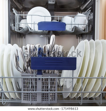 opened dishwasher with clean dishes - stock photo