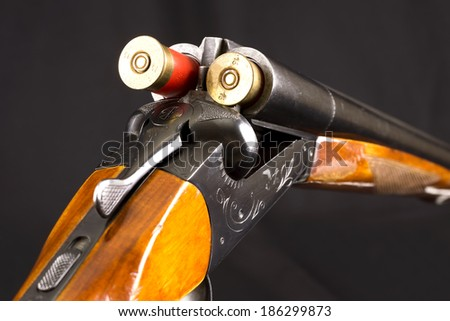 Opened double-barreled hunting gun with two cartridges against black - stock photo