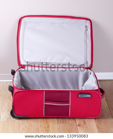 Opened empty red suitcase - stock photo