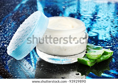 Opened glass jar of cream and aloe on dark blue background with water droplets - stock photo