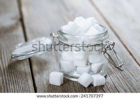 Opened glass jar with lump sugar. - stock photo