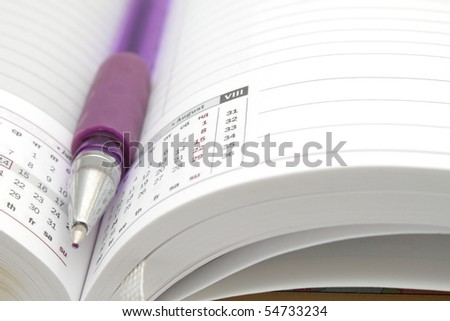 Opened lined diary with a ball pen inside - stock photo