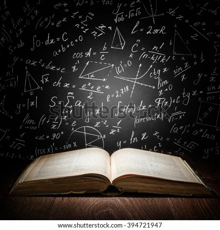 Opened magic book with mathematical formula on a black background. - stock photo