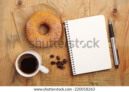 Opened notebook and cup of coffee with donut on wooden desk. Top view - stock photo