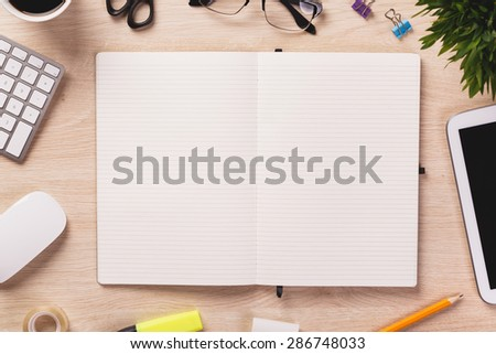 Opened notebook and other office equipment such as computer keyboard, mouse, digital tablet, pencil, mug of coffee and glasses on wooden office desk. - stock photo