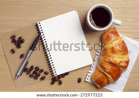 Opened notebook, coffee cup and croissant on desk, top view - stock photo