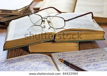 Opened notebook, pen, books and glasses on the wooden table - stock photo