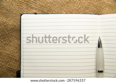 Opened notebook with a blank sheet and pen on the old tissue - stock photo