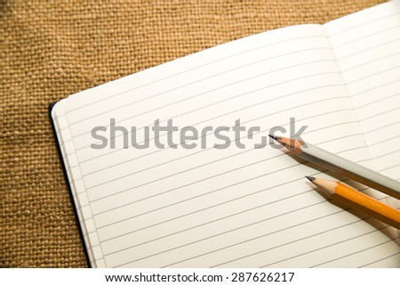 Opened notebook with a blank sheet and pencisl on the old tissue - stock photo