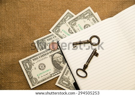 Opened notebook with a blank sheet, keys and money on the old tissue - stock photo