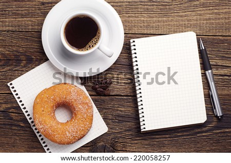Opened notepad and cup of coffee with donut on vintage wooden table. Top view - stock photo