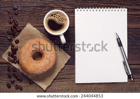 Opened notepad and cup of coffee with donut on vintage wooden table, top view - stock photo