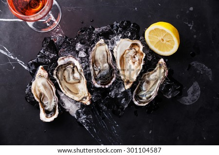 Opened Oysters on dark marble background with ice, lemon and rose wine - stock photo