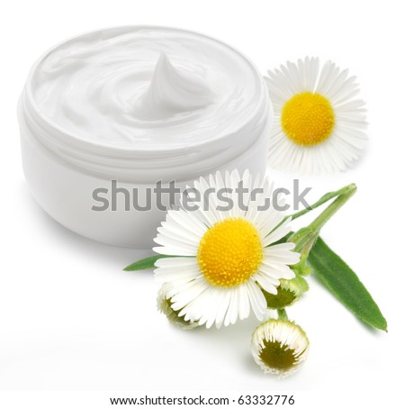 Opened plastic container with cream and camomile on a white background. - stock photo
