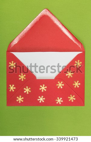 opened red envelope and snowflakes on green background, christmastime - stock photo
