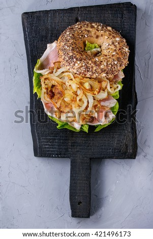 Opened sprinkle seeds Whole Grain bagel with fried onion, green salad and prosciutto ham on black wood chopping board over gray textured background. Top view - stock photo