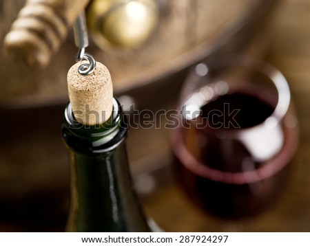 Opening of a wine bottle with corkscrew with wooden barrel on the background. - stock photo