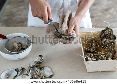 Opening oysters. Shuck oysters - stock photo