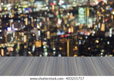 Opening wooden floor, Blurred bokeh business district lights at night, Tokyo Japan - stock photo