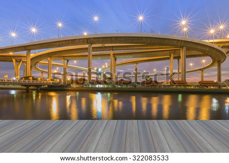 Opening wooden floor, Suspension Bridge across the river at twilight, The Industrial Ring Road (Bangkok, Thailand) - stock photo