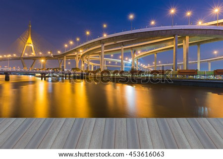 Opening wooden floor, Twilight waterfront over highway interchange connect suspension bridge background - stock photo