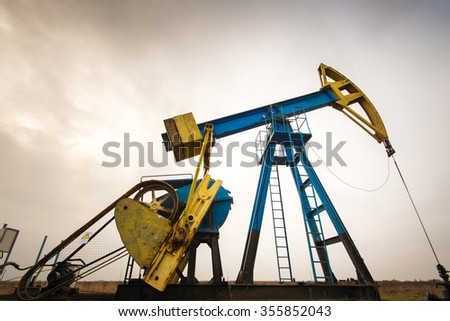 Operating oil and gas well profiled on colorful cloudy sky - stock photo