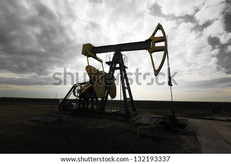 Operating oil well profiled on dramatic cloudy sky, in active oilfield - stock photo