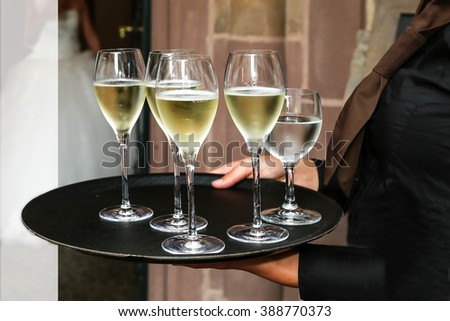 Operation served champagne and water glasses on a tray - stock photo