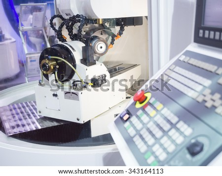 operator grinding cutting tool by CNC grinding machine - stock photo