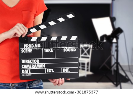 Operator holding clapperboard during the production of the film indoors - stock photo