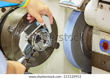 operator measuring cnc grinding part by micrometer - stock photo