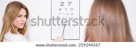 Ophthalmologist using Snellen chart to examine patient's vision - stock photo