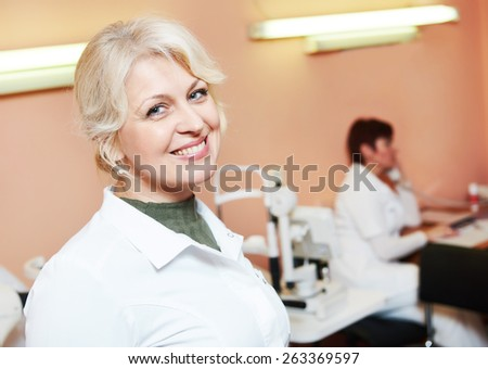 Ophthalmology. portrait of female optometrist optician doctor in eye correction medic clinic  - stock photo