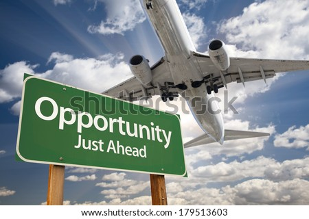 Opportunity Green Road Sign and Airplane Above with Dramatic Blue Sky and Clouds. - stock photo