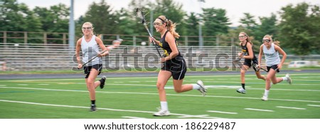 Opposing teams doing battle during a girls Lacrosse game, outdoors on playing field. - stock photo