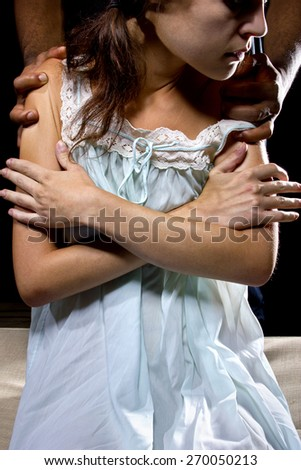 Oppressive man behind a female victim of domestic violence or abuse - stock photo