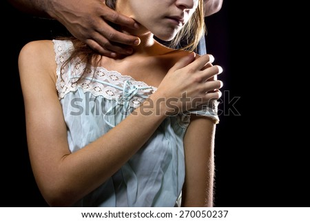 Oppressive man behind a female victim of domestic violence or abuse. Man choking woman on the neck. - stock photo