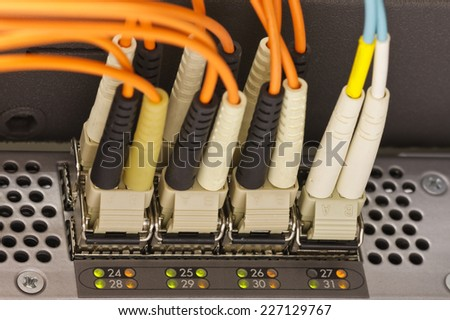 Optical communication cables plugged into the high speed network router - stock photo