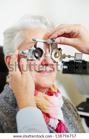 Optician adjusting the trial frame for a senior woman - stock photo