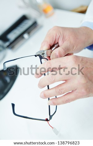 Optician fixing frame of glasses with bending pliers - stock photo