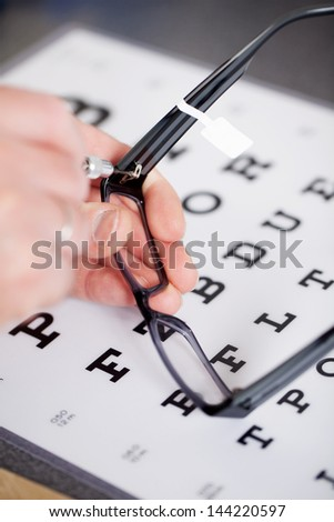 optician fixing frame with snellen chart in background - stock photo