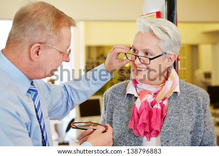 Optician offering consultation to senior woman for new glasses - stock photo