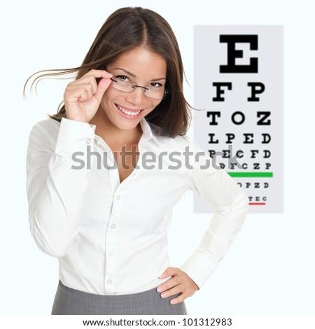 Optician or optometrist showing Snellen eye exam chart wearing eye wear glasses. Female mixed race Caucasian / Asian Chinese model - stock photo