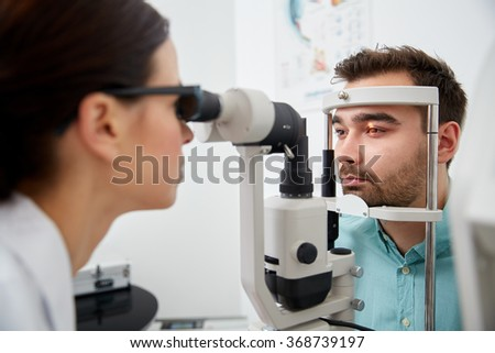 optician with tonometer and patient at eye clinic - stock photo