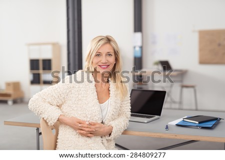 Optimistic Adult Office Lady in Off White Blazer, Sitting at her Table, with Laptop and Notes, with Hands Crossed and Looking at the Camera. - stock photo