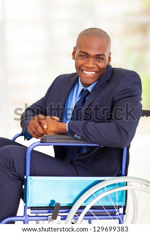 optimistic handicapped african businessman sitting on wheelchair - stock photo