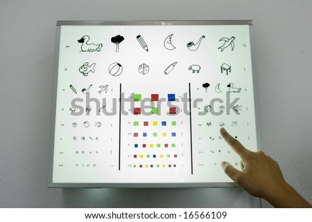 Optometrist finger showing eye chart for children - stock photo
